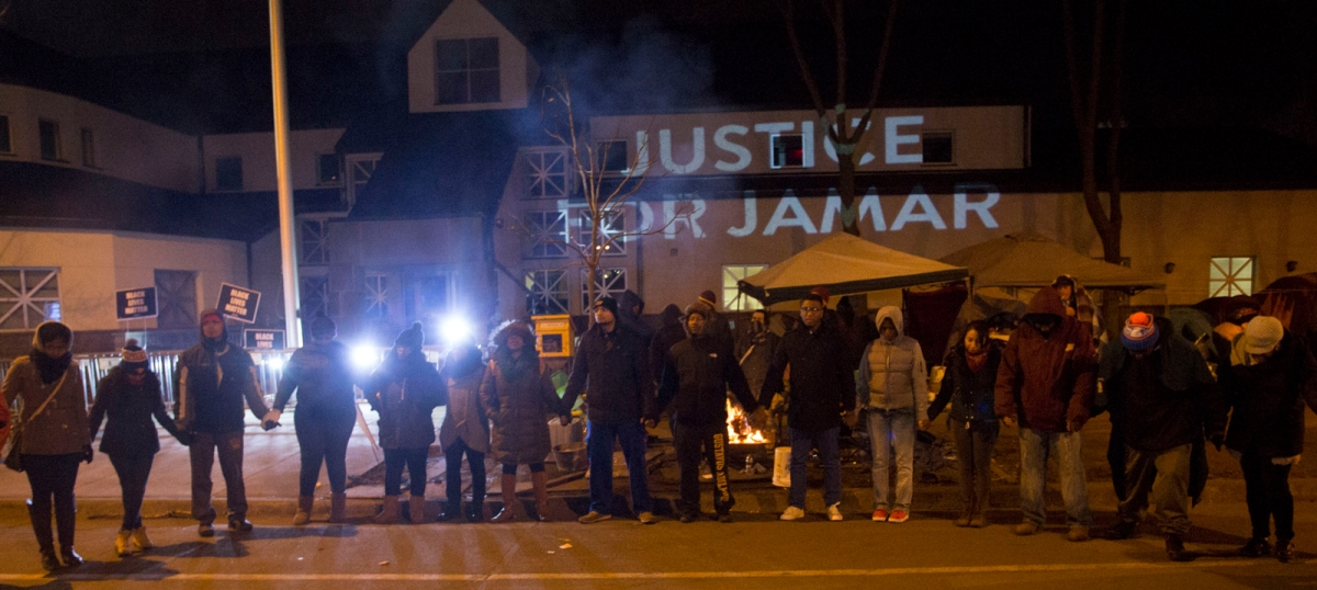 "People gather in front of a ""Justice for Jamar"" projection on side of the 4th police precinct building in North Minneapolis, November 20, 2015"